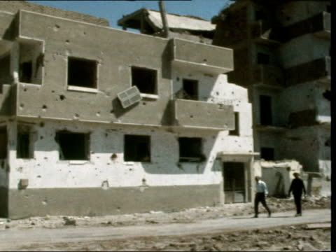 damaged buildings in suez city:; egypt: suez city: ext gv damaged building: pan right to road: gv flats; damaged: side of building gone: rubble from... - barricade stock videos & royalty-free footage