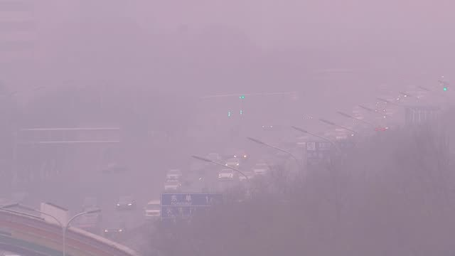 war on pollution starting to have an effect; t30111516 / beijing: ext various of buildings and traffic in city shrouded with a red smog of air... - luftverschmutzung stock-videos und b-roll-filmmaterial