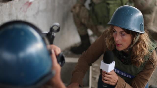 vídeos y material grabado en eventos de stock de prensa de guerra informando detrás de los soldados en la zona de guerra - war
