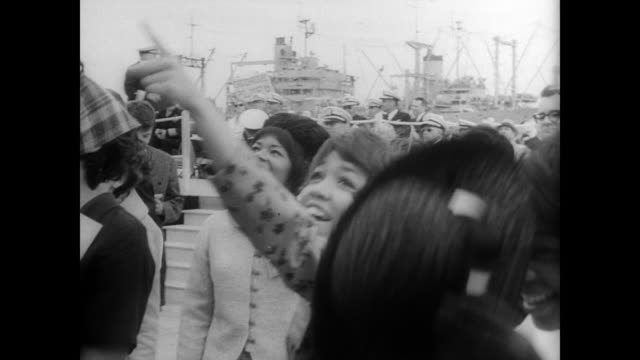 war ship uss enterprise entering san francisco harbor after eight months in vietnam / women on shore wave to sailors on ship / sailors walk down... - moving toward stock videos & royalty-free footage