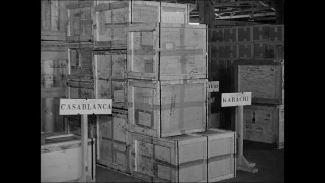 War supplies crates boxes stacked in warehouse w/ destination signs VS Men loading supplies into cargo airplane hold MS Douglas C47 Skytrain taxiing...