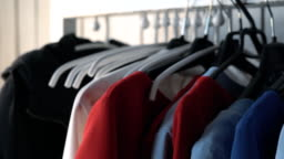 wardrobe hanger with multi-colored clothes in the store. colorful outfits hang on a hanger. a woman's hand takes a hanger with a red dress. pulls out of the closet FullHD