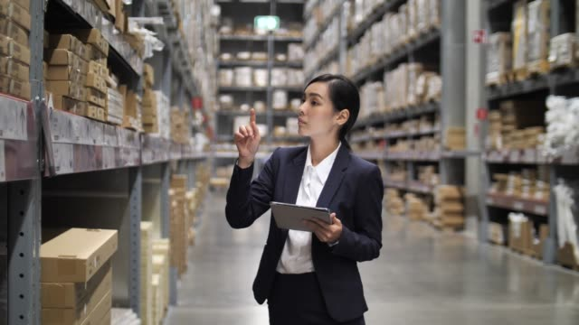 vídeos de stock e filmes b-roll de warehouse businesswoman manager using her digital tablet in warehouse - e commerce