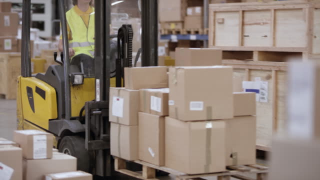 warehouse employee driving a reach truck with packages on a pallet through a warehouse - polo shirt stock videos & royalty-free footage