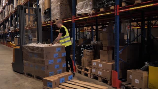 stockvideo's en b-roll-footage met de werknemer van het pakhuis in weerspiegelende eenvormige drijfvorftruck. essentiële arbeider in de industrie tijdens coronaviruspandemie - merchandise