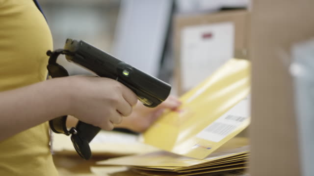 pan warehouse employee scanning envelopes with a handheld barcode scanner - built structure stock videos & royalty-free footage
