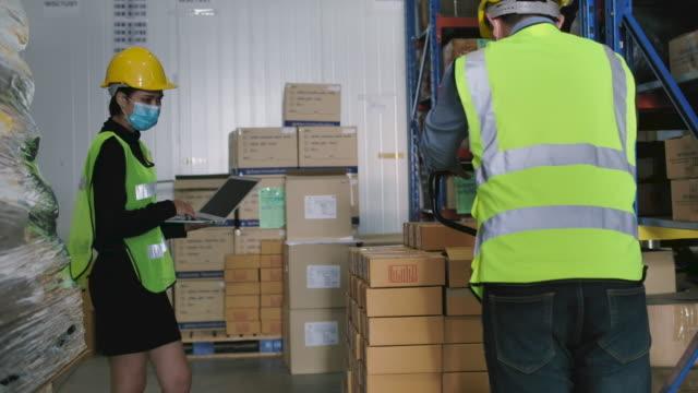 lagermitarbeiter mit einer palettenbuchse, um gestapelte kisten von kisten wegzunehmen. - box container stock-videos und b-roll-filmmaterial