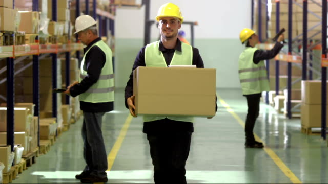 warehouse employee walking with a box - carrying 個影片檔及 b 捲影像
