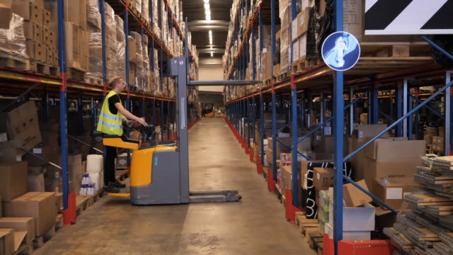 stockvideo's en b-roll-footage met magazijnmedewerker werkzaam in distributie-en logistiek centrum-slow motion video - heftruck