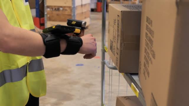 vidéos et rushes de employé d'entrepôt travaillant dans le centre de distribution et de logistique, utilisant le scanner de code à barres - vidéo de ralenti - paquet