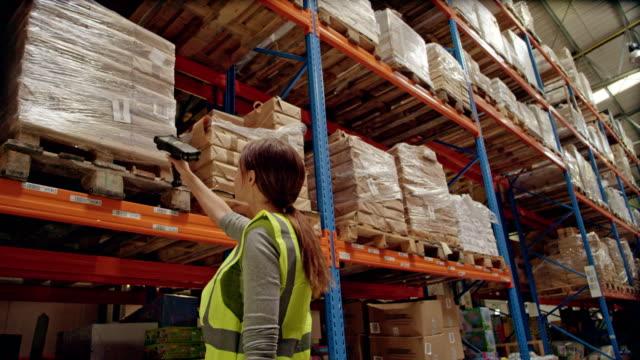 Warehouse female worker using bar code reader
