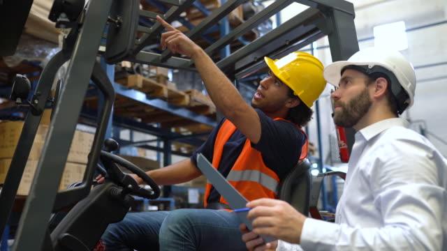 lagervorarbeiter diskutiert lieferungen mit gabelstaplerfahrer - dockarbeiter stock-videos und b-roll-filmmaterial