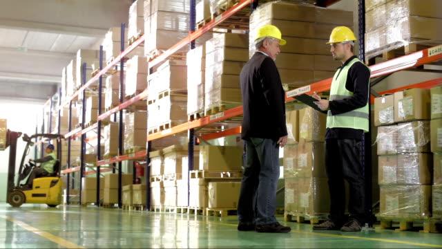倉庫・フォーマン、従業員が話し - 倉庫作業員点の映像素材/bロール