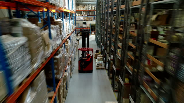 warehouse logistic center. worker driving on a forklift - deposito video stock e b–roll