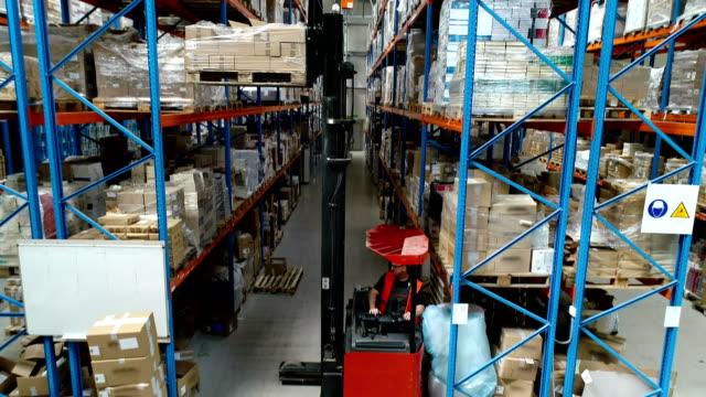 lager-logistikzentrum. arbeiter auf einem gabelstapler fahren - hubwagen stock-videos und b-roll-filmmaterial