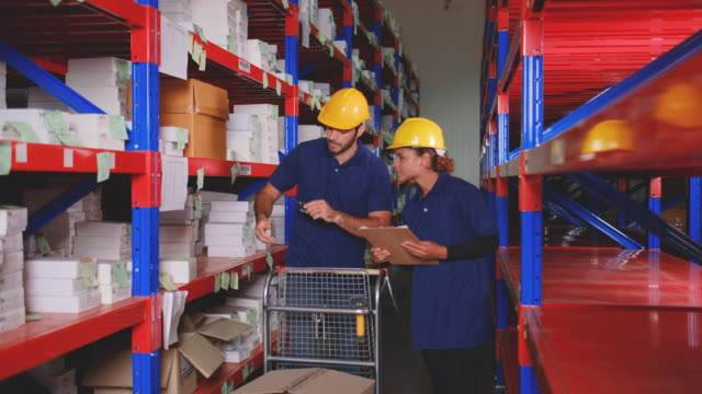 warehouse man and woman worker help to move box on the shelf - mitarbeiterengagement stock-videos und b-roll-filmmaterial