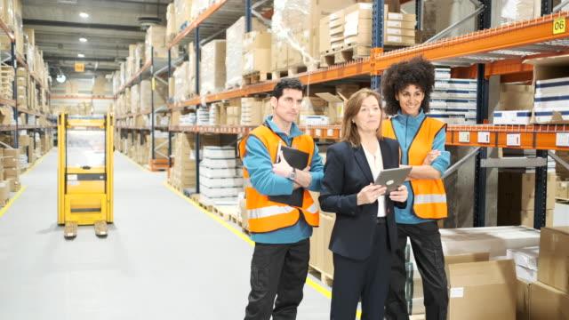 倉庫マネージャーと立ち上がりチームミーティングの 2 人の作業者。 - 倉庫作業員点の映像素材/bロール