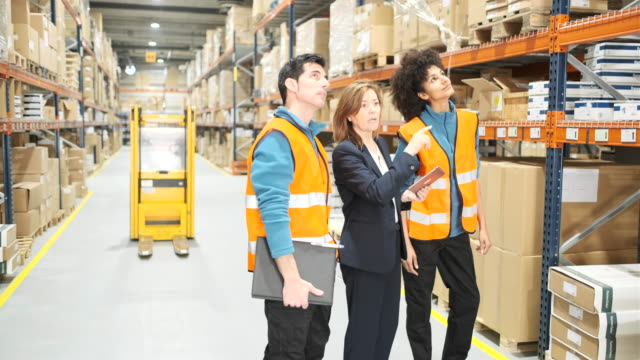 warehouse manager and two workers in a standing up team meeting. - foreman stock videos & royalty-free footage