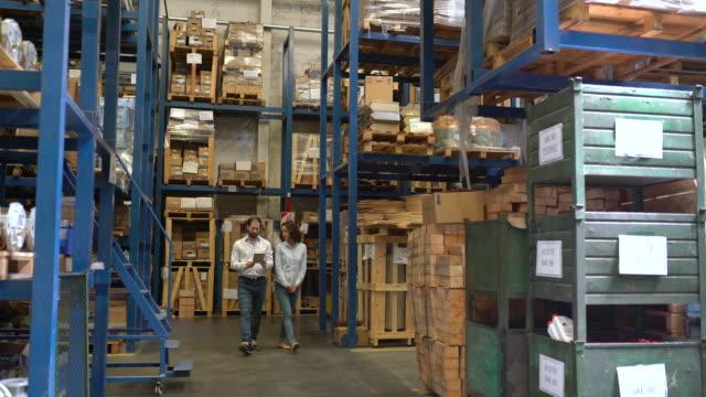 vídeos y material grabado en eventos de stock de gerente de almacén comprobando el inventario con el colega - negocio global