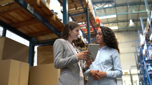 lagerleiter diskutiert lieferplan mit kollegen - distribution warehouse stock-videos und b-roll-filmmaterial