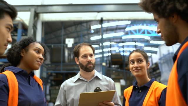 lagerleiter diskutiert mit mitarbeitern über die lieferung von produkten - distribution warehouse stock-videos und b-roll-filmmaterial