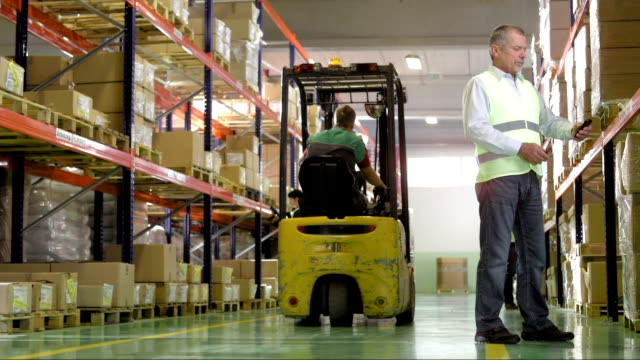 warehouse manager scans codes with smartphone - forklift stock videos & royalty-free footage