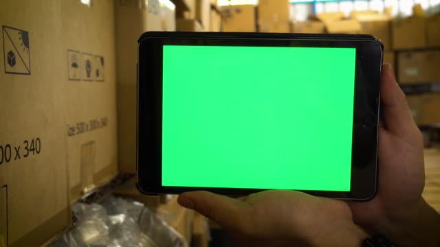 lagerhaus überprüft inventar auf digitalem tablet-greenscreen - distribution warehouse stock-videos und b-roll-filmmaterial