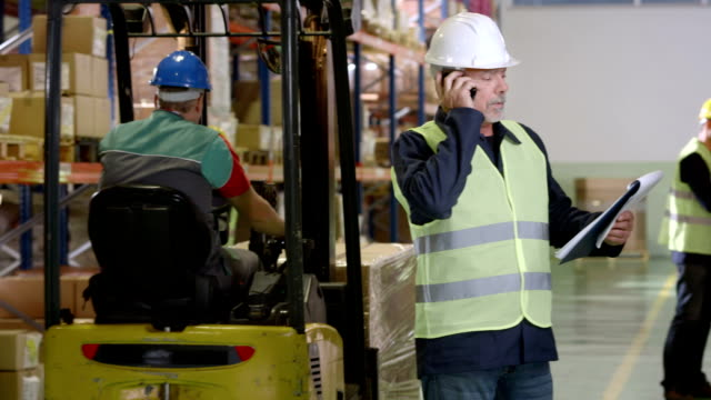 warehouse supervisor talking on the mobile phone - comment box stock videos & royalty-free footage