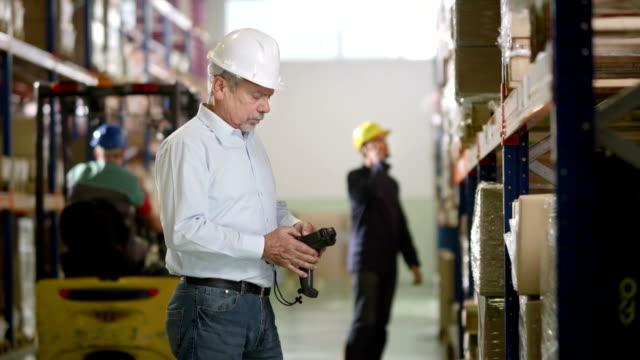 vídeos de stock e filmes b-roll de supervisor de armazém com leitor de código de barras - capacete