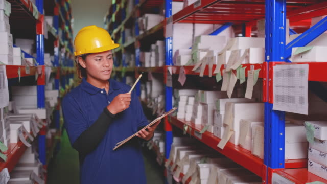 warehouse woman worker walk through way between shelf and checking stock - mitarbeiterengagement stock-videos und b-roll-filmmaterial