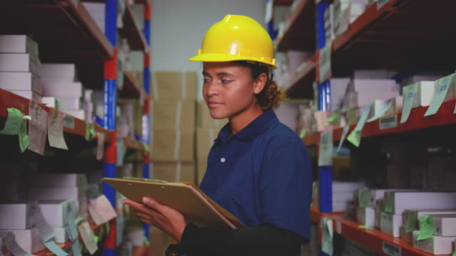 warehouse woman worker walk through way between shelf in workplace area and also checking stock - mitarbeiterengagement stock-videos und b-roll-filmmaterial