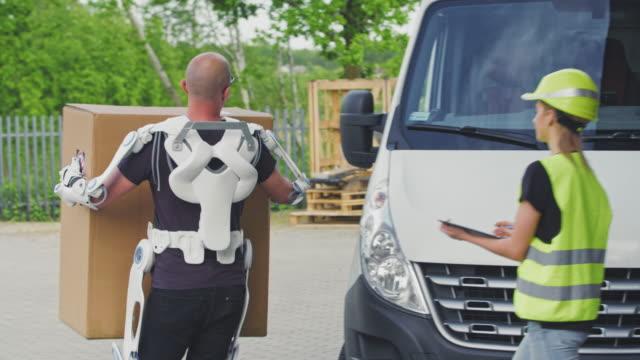 vídeos de stock, filmes e b-roll de funcionário do armazém trazendo suprimentos da van de entrega. usando exoesqueleto alimentado. close-ups - mobília