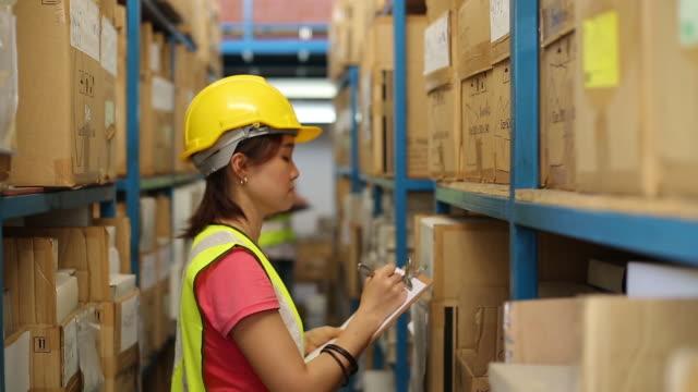 vídeos y material grabado en eventos de stock de trabajador de almacén verificando productos de stock - recibir