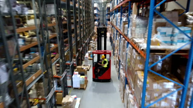 warehouse worker driving on a forklift. drone point of view - deposito video stock e b–roll