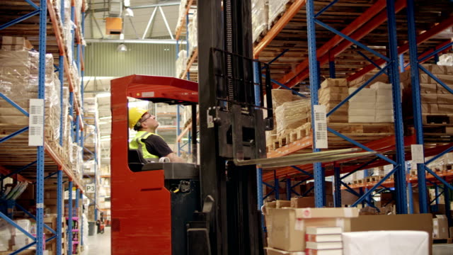 warehouse worker driving on a forklift - forklift truck stock videos and b-roll footage