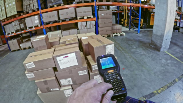 POV Warehouse worker entering data into a handheld scanner before scanning the packages