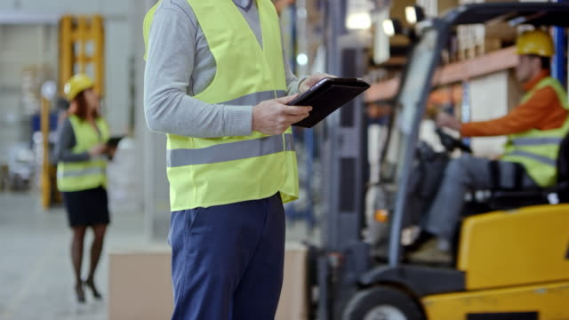 warehouse worker holding a tablet while standing in the warehouse - forklift truck stock videos and b-roll footage
