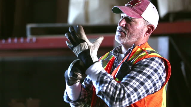 warehouse worker in reflective vest, putting on gloves - protective glove stock videos & royalty-free footage