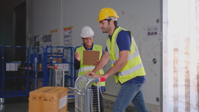 warehouse worker man use cart to carry product box or packaging com inside cargo factory - mitarbeiterengagement stock-videos und b-roll-filmmaterial
