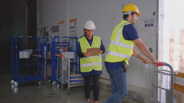 warehouse worker man use cart to carry product box or packaging out of cargo factory - mitarbeiterengagement stock-videos und b-roll-filmmaterial
