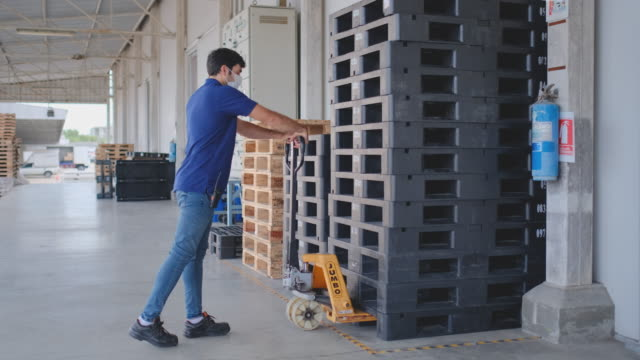 warehouse worker man use mobile lifting machine to move palle - mitarbeiterengagement stock-videos und b-roll-filmmaterial
