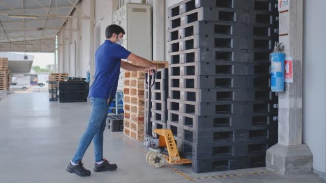 warehouse worker man use mobile lifting machine to move palle - 従業員エンゲージメント点の映像素材/bロール