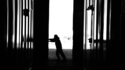 Warehouse Worker Opening Metal Door. Black and White Tone.