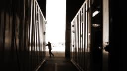 Warehouse Worker Opening Metal Door. Sepia Tone.
