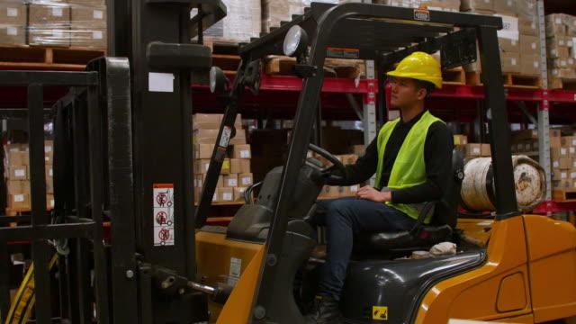 ワーカーと見上げるとフォーク リフトを営業倉庫します。 - 倉庫作業員点の映像素材/bロール