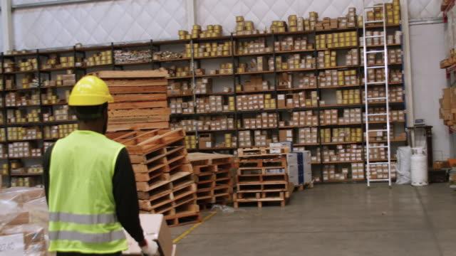 倉庫の労働者手トラックのボックスを押す - 倉庫作業員点の映像素材/bロール