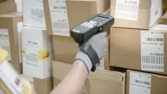 warehouse worker scanning packages with a handheld barcode scanner - freight transportation stock videos & royalty-free footage