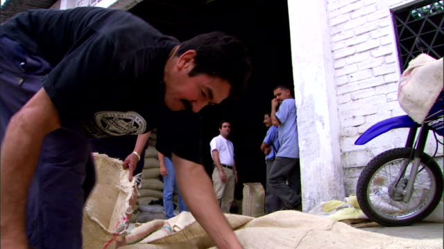 a warehouse worker scoops grain and pours it into a burlap bag. - 麻袋点の映像素材/bロール