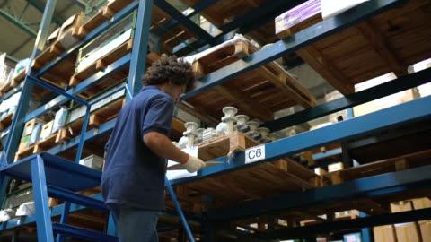 vídeos y material grabado en eventos de stock de trabajador de almacén haciendo inventario - estante muebles