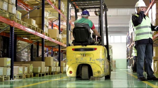 倉庫労働者の携帯電話で話している - 倉庫作業員点の映像素材/bロール
